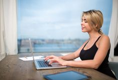 Smiling woman office worker keyboarding on modern laptop computer, sitting at table near window. Cheerful female secretary typing on portable net-book Royalty Free Stock Photos