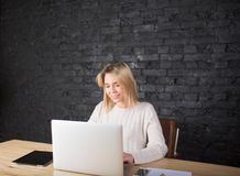 Beautiful smiling businesswoman keyboarding on laptop computer, working distance with colleague. Cheerful female secretary working on net-book during work day Royalty Free Stock Photo