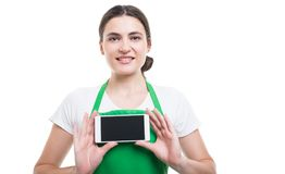 Cheerful female seller showing modern cellphone royalty free stock photos
