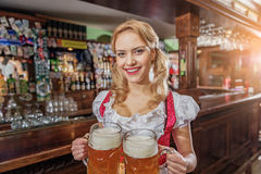 Cheerful female serving alcohol in pub Royalty Free Stock Images