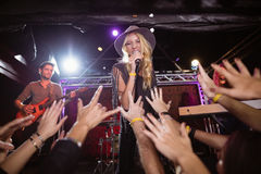 Cheerful female singer performing on stage at nightclub. During music festival Royalty Free Stock Photos
