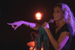 Cheerful female singer pointing while performing in nightclub Royalty Free Stock Photography
