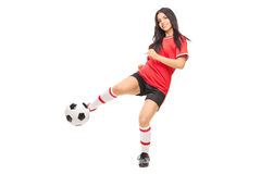 Cheerful female soccer player shooting a ball Stock Photos