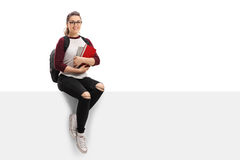 Cheerful female student with backpack and books sitting on panel Royalty Free Stock Photography