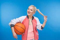 Cheerful female student holding basketball ball. Over blue background Stock Images