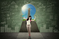 Cheerful female student in the keyhole Royalty Free Stock Image