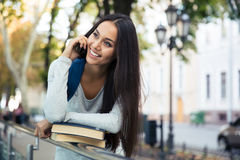 Cheerful female student talking on the phone Royalty Free Stock Photography