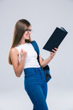 Cheerful female teenager reading book Stock Photo