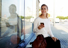 Cheerful female tourist using mobile phone for view map via network and continue her walk in strange city, Stock Photo