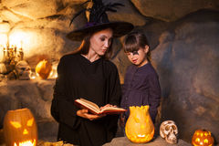Cheerful female wizard is teaching child to Royalty Free Stock Photography