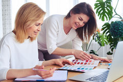 Cheerful females working with catalog of color palette. Close-up of cheerful females working with catalog of color palette royalty free stock photos