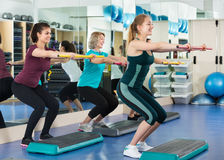 Cheerful females working out on aerobic step platform. Smiling cheerful females working out on aerobic step platform in modern gym Royalty Free Stock Photos