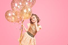 Cheerful festive girl with bunch of balloons. Cheerful young girl in glittering golden dress holding golden balloons on pink background Royalty Free Stock Photography