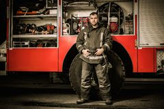 Cheerful firefighter near truck Royalty Free Stock Images