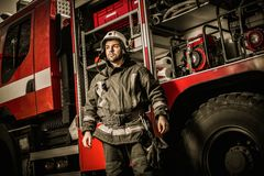 Cheerful firefighter near truck Stock Images