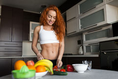 Cheerful fit adult woman cooking salad Royalty Free Stock Photos