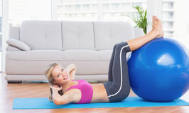 Cheerful fit blonde doing sit ups with exercise ball Royalty Free Stock Photos