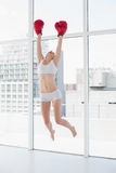 Cheerful fit brown haired model in sportswear jumping and wearing red boxing gloves Stock Images