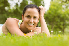 Cheerful fit brunette lying on the grass Stock Image