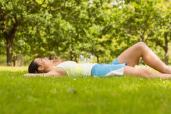 Cheerful fit brunette lying and relaxing on the grass Stock Photography