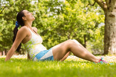 Cheerful fit brunette relaxing on the grass Stock Image