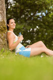 Cheerful fit brunette sitting against a tree holding a bottle Royalty Free Stock Image