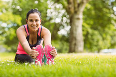 Cheerful fit brunette stretching on the grass Royalty Free Stock Images