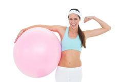 Cheerful fit woman flexing muscles  with fitness ball Royalty Free Stock Photography