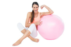 Cheerful fit woman flexing muscles  by fitness ball Royalty Free Stock Image