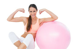 Cheerful fit woman flexing muscles  by fitness ball Stock Photo