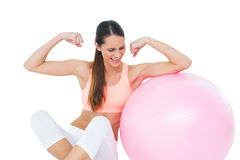 Cheerful fit woman flexing muscles by fitness ball. Cheerful fit young woman flexing muscles by fitness ball over white background stock photography