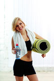 Cheerful fit woman holding a bottle with water and yoga mat Stock Photo