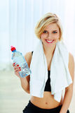 Cheerful fit woman holding a bottle with water Stock Photo