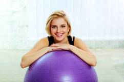 Cheerful fit woman leaning on the fitball Stock Photo