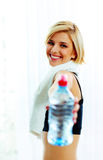 Cheerful fit woman passing a bottle of water to you Royalty Free Stock Photography