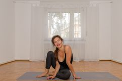 Smiling woman exercising yoga on mat at home. Cheerful fit woman practising yoga on mat at home Stock Image