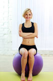 Cheerful fit woman sitting on the fitball Royalty Free Stock Photo