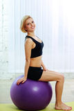 Cheerful fit woman sitting on the fitball Stock Images