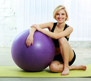 Cheerful fit woman sitting on the floor with fitball Stock Photography