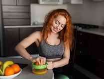 Cheerful fit woman squeezing juice royalty free stock photography