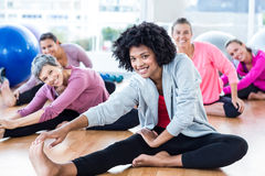 Cheerful fit women touching toes. Portrait of cheerful fit women touching toes in fitness studio Stock Images