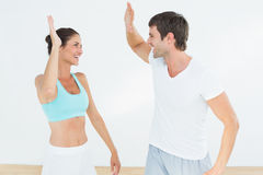 Cheerful fit young couple giving high five Royalty Free Stock Image