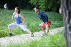 Cheerful fit young couple stretching Stock Photo