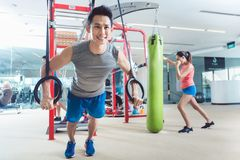 Fit young man exercising with gymnastic rings in a trendy fitness center stock photography