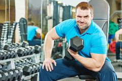 Cheerful fitness bodybuilding trainer with dumbbell at gym Stock Photo