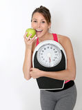 Cheerful fitness girl with green apple succeeding diet Royalty Free Stock Image