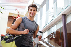 Cheerful fitness man with bottle of water walking on training. Cheerful young fitness man with bag and bottle of water walking on training in gym stock photo