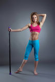 Cheerful fitness trainer posing with fitbar Royalty Free Stock Image