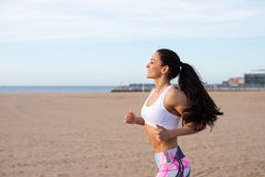 Cheerful fitness woman running at the beach Royalty Free Stock Images