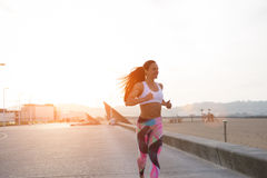 Cheerful fitness woman running at sunset Stock Photo